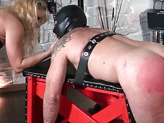 Female dom penalizing slave on smacking bench by crop and cane
