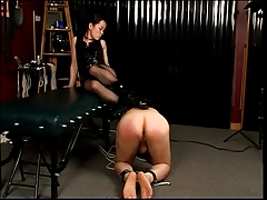 Dominatrix steps on his goods with heels