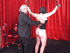 Spread-eagled  female in leather mask and spandex hood gets flagellated on her bum